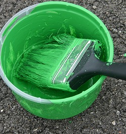 can of green paint and brush