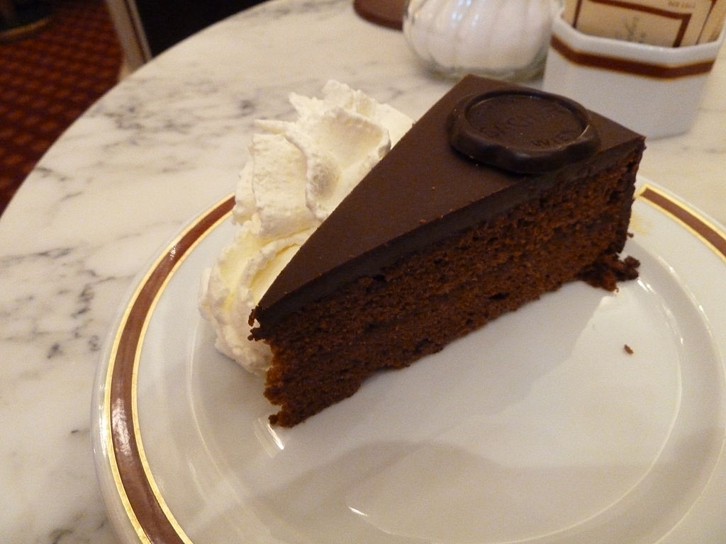 Slice of Sachertorte with whipped cream on the side.